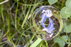 Burbuja de jabón hermosa en la hierba con la reflexión del fotógrafo foto de archivo