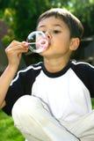 Burbuja que sopla del muchacho joven Imagen de archivo