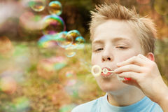 Burbuja que sopla del niño masculino al aire libre Imagen de archivo
