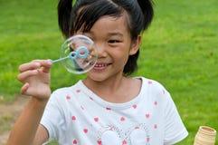 Burbujas chinas del soplo de la muchacha Imagenes de archivo