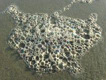 Burbujas coloridas de la espuma de la ola oceánica en la arena de la playa Fotos de archivo libres de regalías
