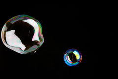 Burbujas de jabón brillantes delante de un fondo oscuro Foto de archivo libre de regalías