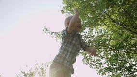 Burbujas de jabón de cogida del niño pequeño feliz en la cámara lenta HD lleno del parque del verano almacen de video