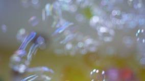 Burbujas de jabón coloridas que flotan en la cámara lenta metrajes