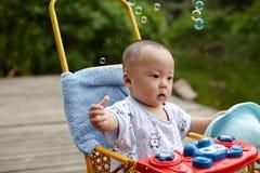 Burbujas de jabón de cogida del niño Imagenes de archivo