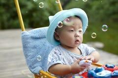 Burbujas de jabón de cogida del niño Foto de archivo