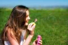 Burbujas de jabón de la chica joven que soplan Foto de archivo