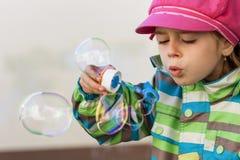 Burbujas de jabón de la chica joven que soplan Imagenes de archivo
