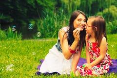 Burbujas de jabón de la madre que soplan y del niño al aire libre Foto de archivo libre de regalías