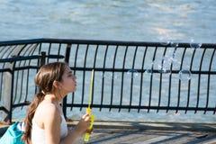 Burbujas de jabón de la muchacha que soplan Imágenes de archivo libres de regalías