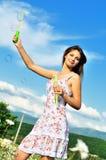 Burbujas de jabón de la muchacha que soplan adolescente Foto de archivo