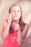 Burbujas de jabón de la muchacha que soplan adolescente feliz Imágenes de archivo libres de regalías