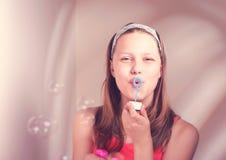 Burbujas de jabón de la muchacha que soplan adolescente feliz Foto de archivo
