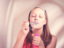 Burbujas de jabón de la muchacha que soplan adolescente feliz Imagen de archivo