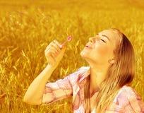 Burbujas de jabón de la muchacha que soplan en campo de trigo Imagen de archivo libre de regalías