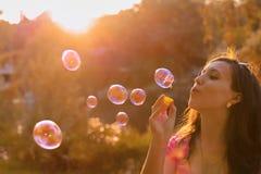 Burbujas de jabón de la muchacha que soplan en la puesta del sol Fotografía de archivo