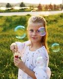 Burbujas de jabón de la muchacha que soplan rubia feliz imagenes de archivo