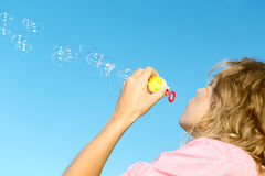 Burbujas de jabón de la muchacha que soplan rubia joven hermosa Imagen de archivo