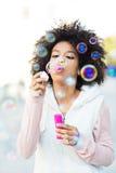 Burbujas de jabón de la mujer del Afro que soplan Imagen de archivo libre de regalías