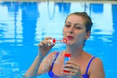 Burbujas de jabón de la mujer que soplan Imagenes de archivo