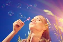 Burbujas de jabón de la mujer que soplan bonita Imagenes de archivo