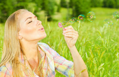 Burbujas de jabón de la mujer que soplan bonita en parque Fotografía de archivo libre de regalías