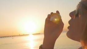 Burbujas de jabón de la mujer que soplan en la puesta del sol almacen de video