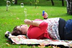 Burbujas de jabón de la mujer que soplan feliz Imagen de archivo libre de regalías