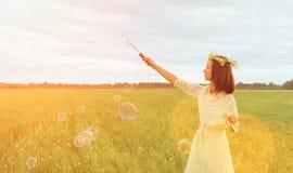 Burbujas de jabón de la mujer que soplan hermosa en el verano al aire libre Fotos de archivo