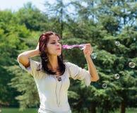 Burbujas de jabón de la mujer que soplan joven Fotos de archivo