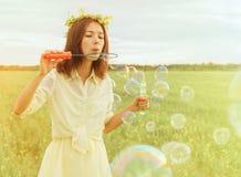 Burbujas de jabón de la mujer que soplan joven en verano Fotos de archivo libres de regalías