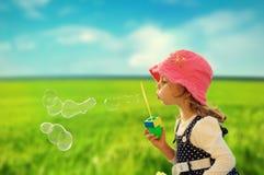 Burbujas de jabón de la niña que soplan Imágenes de archivo libres de regalías