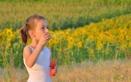 Burbujas de jabón de la niña que soplan fotografía de archivo