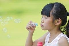 Burbujas de jabón de la niña que soplan en el parque Imagenes de archivo