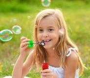 Burbujas de jabón de la niña que soplan feliz Imagenes de archivo