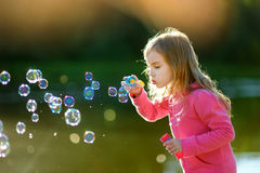 Burbujas de jabón de la niña que soplan preciosa divertida imágenes de archivo libres de regalías