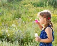 Burbujas de jabón de la pequeña muchacha que soplan linda Imágenes de archivo libres de regalías