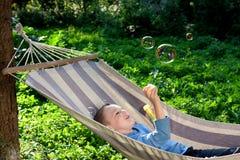 Burbujas de jabón del muchacho que soplan hermoso Foto de archivo libre de regalías