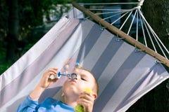 Burbujas de jabón del muchacho que soplan hermoso al aire libre Imagenes de archivo