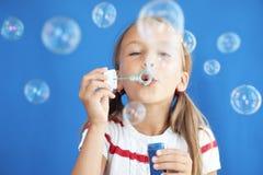 Burbujas de jabón del niño que soplan fotografía de archivo