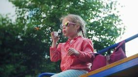 Burbujas de jabón del niño que soplan feliz en parque de la primavera metrajes