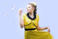 Burbujas de jabón hermosas de la mujer que soplan joven Imagenes de archivo
