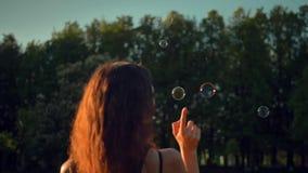 Burbujas de jabón jovenes hermosas del soplo y de la explosión de la señora del redhair al aire libre metrajes