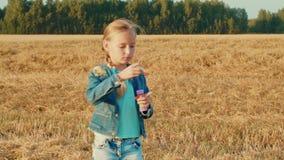 Burbujas de jabón de la chica joven que soplan hermosa durante la rotación en campo del otoño almacen de video
