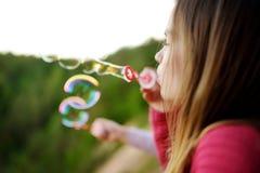 Burbujas de jabón de la niña que soplan linda en un aire libre de la puesta del sol en día de verano hermoso fotos de archivo libres de regalías
