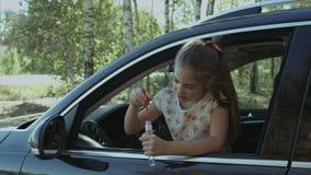 Burbujas de jabón de la pequeña muchacha que soplan linda en el coche almacen de metraje de vídeo