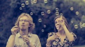 Burbujas de jabón de los pares que soplan, divirtiéndose imagen de archivo libre de regalías