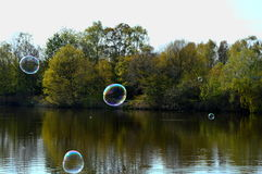 Burbujas de jabón sobre el lago Fotos de archivo libres de regalías