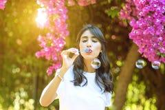 Burbujas de jab?n hermosas felices de la mujer que soplan joven al aire libre foto de archivo