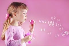 Burbujas de jabón de la muchacha que soplan Imagen de archivo